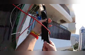 男子高空跳伞挂公寓外墙