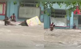 社区人员洪水中用横幅救人
